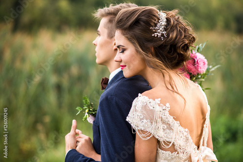 Foto Bride and groom embracing in the park