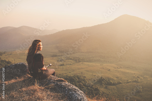 Fotografiet  Hipster young girl with backpack enjoying sunset on peak of foggy mountain