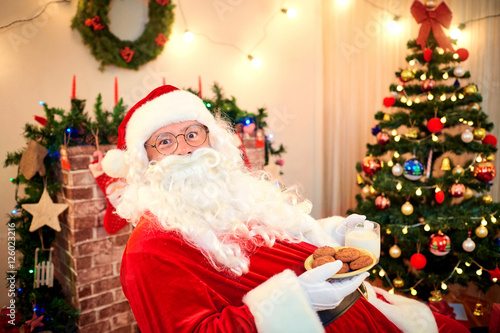 Santa With Cookies And Milk In The Hands In The Room With The Ch