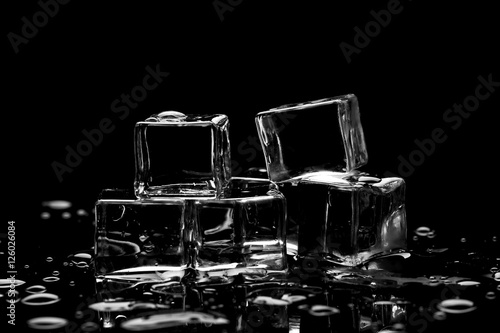 Photo  Wet ice cubes on black background with water drops and reflections