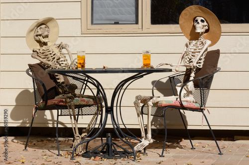 Afternoon tea shared between friends: Skeletons in hats drinking iced tea while sitting at a table outdoors
