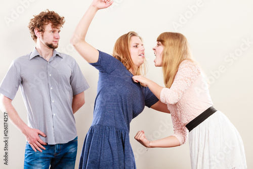 Fotografie, Obraz  Aggressive mad women fighting over man.