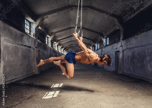sportowa-miesniowa-samiec-pozuje-z-gimnastycznymi-pierscionkami