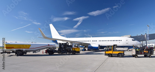 Foto  Refueling an airplane at the airport with a tanker truck // Betanken eines Flugz