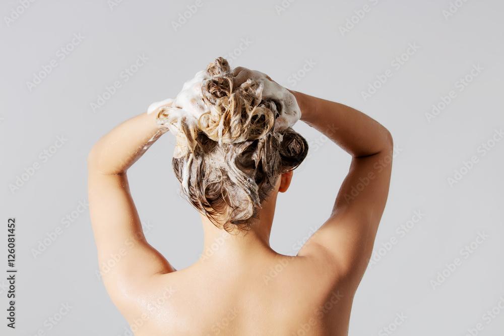 Fototapeta Woman washing her blond hair
