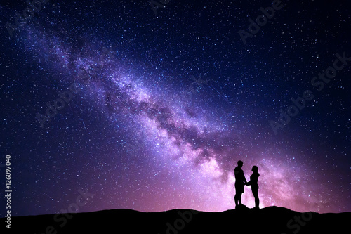 In de dag Groene koraal Milky Way with silhouette of people. Landscape with night sky with stars and standing man and woman holding hands on the mountain. Hugging couple against purple milky way. Beautiful galaxy. Universe