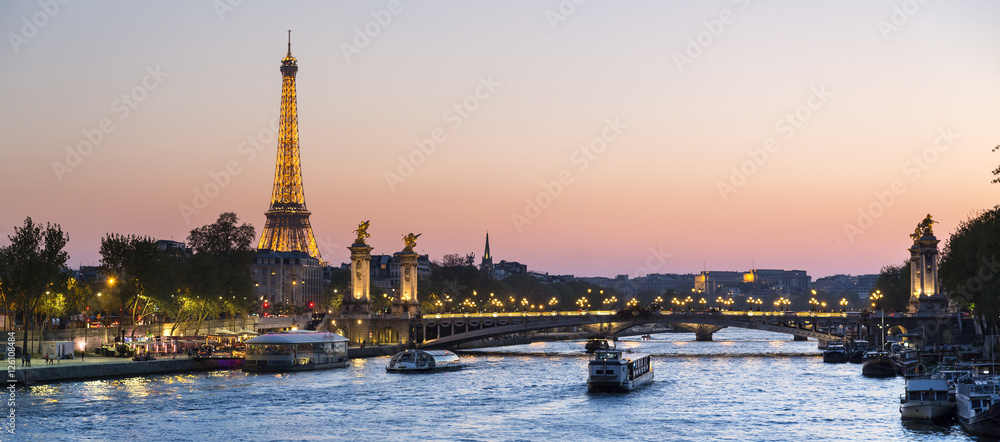 Paris, traffic on the Seine river at sunset, with Eiffel tower i