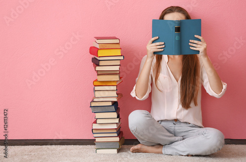 Woman sitting on a floor and holding book in front of face on pink background