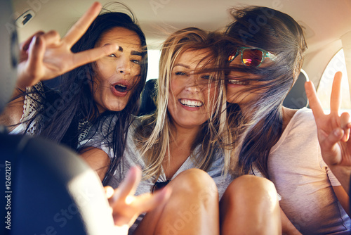 canvas print motiv - Flamingo Images : Three beautiful female friends make peace signs