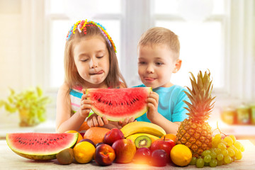 Fototapeta Owoce Happy kids eating watermelon with fruits in kitchen