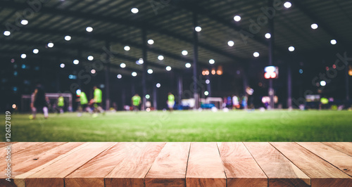 Photo  Wood table top with blur football (soccer) field background.