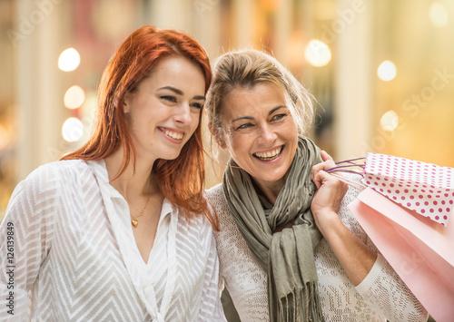 Plakat W mieście matka i jej córka trzymają torby na zakupy i chodzą po ulicy. Światła sklepów w tle