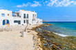 A view of beach in Naoussa port with traditional white Greek architecture, Paros island, Cyclades, Greece