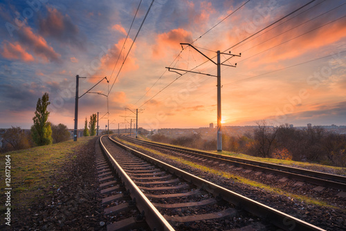 Poster Voies ferrées Railroad against beautiful sky at sunset. Industrial landscape with railway station, colorful blue sky with red clouds, trees and green grass, yellow sunlight. Railway junction. Heavy industry