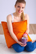 Smiling young woman sitting on a white floor with pillow