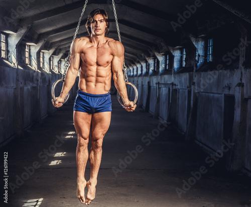 Tuinposter Gymnastiek Athletic gymnast exercising on stationary rings.