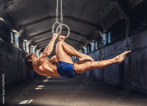 Photo sur Toile Gymnastique Athletic gymnast exercising on stationary rings.