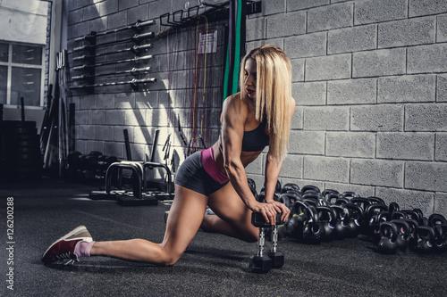 sportowa-kobieta-siedzi-na-podloga-w-gym-klubie