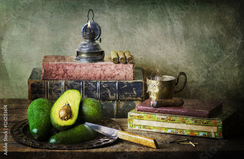 Fotografía  Still Life with fresh avocados placed in vintage tray with old knife, box of cigar, cup of hot coffee, old books and candle on rustic wooden table