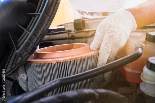 Fotografia, Obraz  auto mechanic wearing protective work gloves holding a dirty, ai