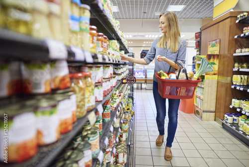 Fotomural  Woman buying products in food aisle
