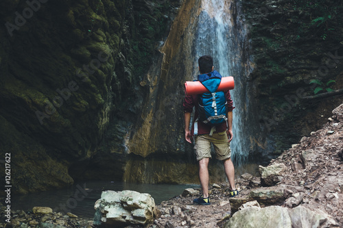 Photo  Man next to a waterfall after mountain trekking