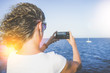Summer sunny day, rear view, young woman, dressed in white t-shirt, standing on the beach and take pictures smartphone. In the background boat in the sea. Girl using the gadget.