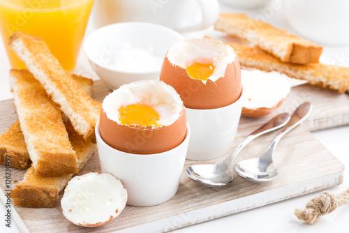 Plakat gotowane jajka i grzanki na drewnianej desce