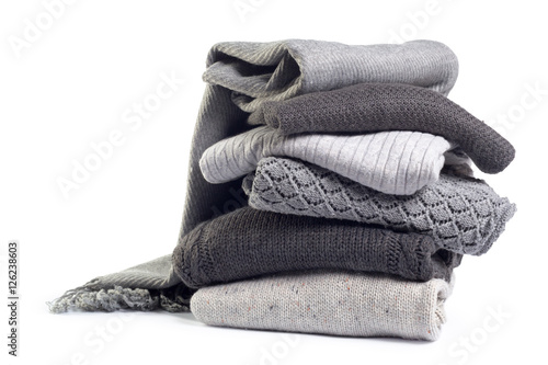 Photo  Stack of various sweaters isolated on white background