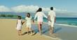 Happy family walking down the beach