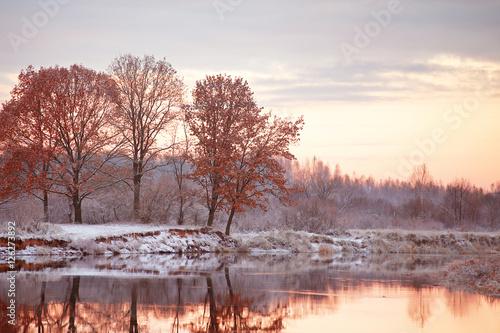 Cloudy autumn dawn. First snow on the autumn river. Oaks on rive Canvas Print