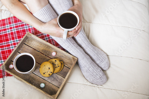 A cup of coffee or hot chocolate and female feet with socks on..