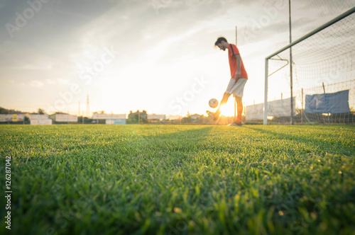 Plakat Gracz piłki nożnej drybling z piłką przy stadium.