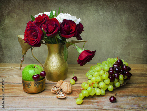 Still life with beautiful bouquet of red and white roses placed together in vintage golden tea pot,bunch of grapes, cherries,green apple and walnut on rustic wooden table. - 126295841