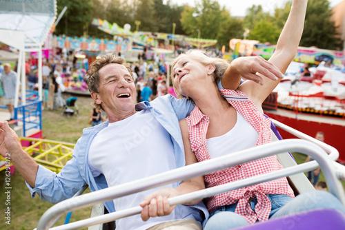 Poster Amusementspark Senior couple on a ride in amusement park