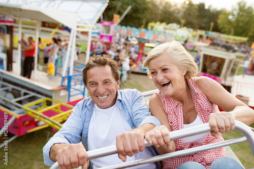 Poster Attraction parc Senior couple on a ride in amusement park