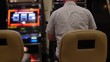 Man gambling at a slot machine in a casino