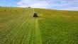 Aerial farmer cuts the grass on field by ocean cove