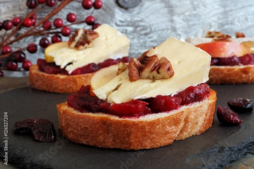 Foto op Canvas Voorgerecht Crostini appetizers with cranberry sauce, apples, brie and pecans on slate server