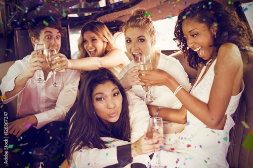 Composite image of happy friends drinking champagne