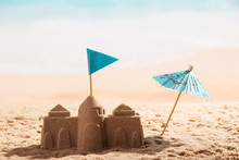 Castle In Sand, Flag And Umbrella Close-up On Sea.