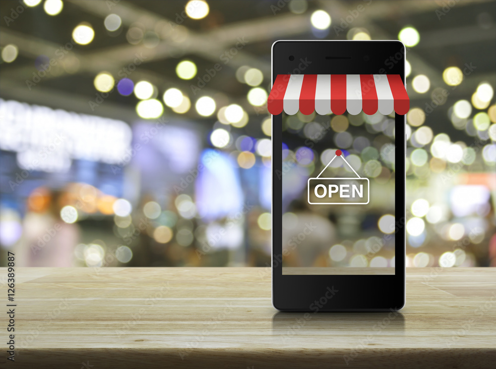 Fototapeta Modern smart mobile phone with on line shopping store graphic an