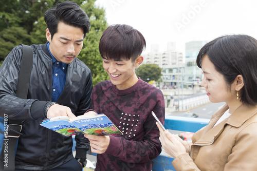 Fotografía  仲間 グループ 3人 男女 東京観光 原宿駅前 ガイドブックを観ながら 女性スマホで検索