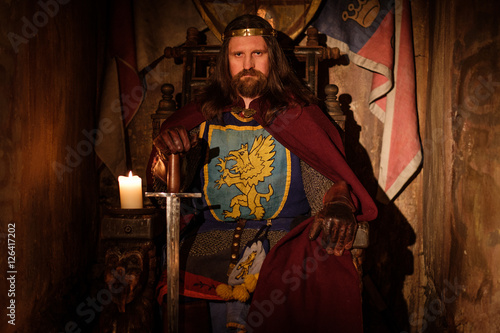 Medieval king on throne in ancient castle interior. Fototapete