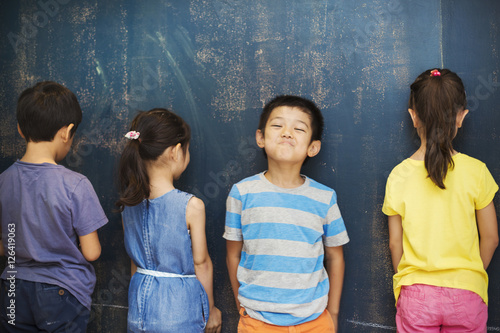 A group of children in school. Four children standing by the blackboard.
