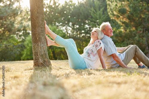 Photo  Senioren Paar sitzt Rücken an Rücken im Gras