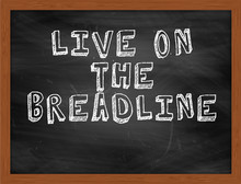 LIVE ON THE BREADLINE Handwritten Text On Black Chalkboard