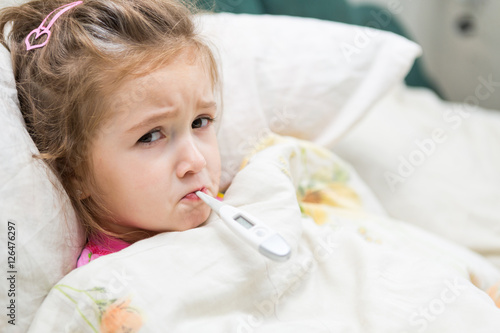 Fotografia  Sick little girl holding thermometer laying in bed with grumpy face