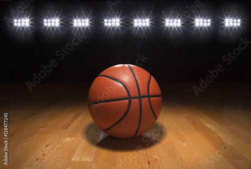 Photo  Basketball on wood floor beneath bright lights