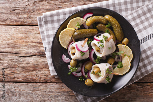 Fotografie, Obraz  rolls of marinated herring with olives, onions, pickles and lemon close-up on a plate
